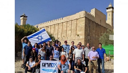 Im Tirtzu college student organization pose on the steps of the Ma'arah HaMachepela (Tomb of the Patriarchs and Matriarchs)