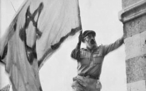 Rabbi Goren holding the Israeli flag as he liberated Hebron in June of 1967