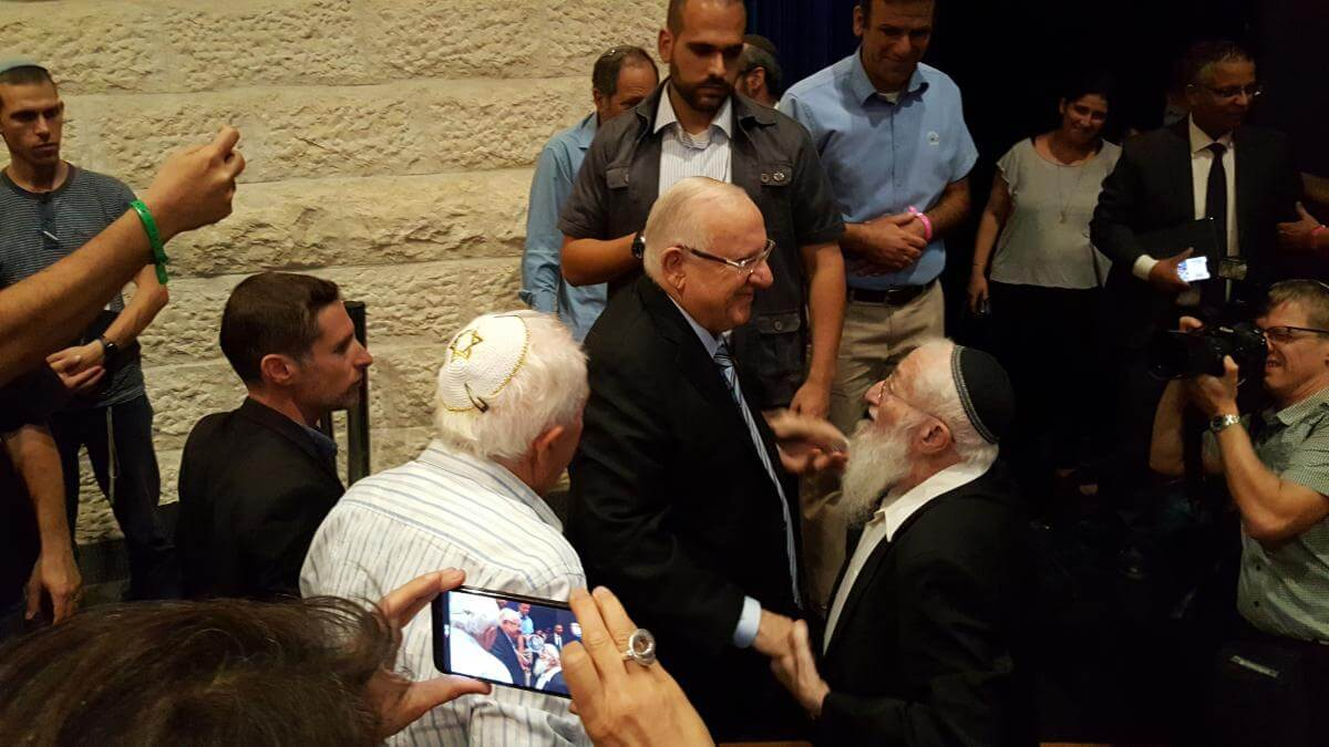 President Reuven Rivlin shakes hands with Hebron pioneer Rabbi Eliezer Waldman, as Yossi Kruchik looks on