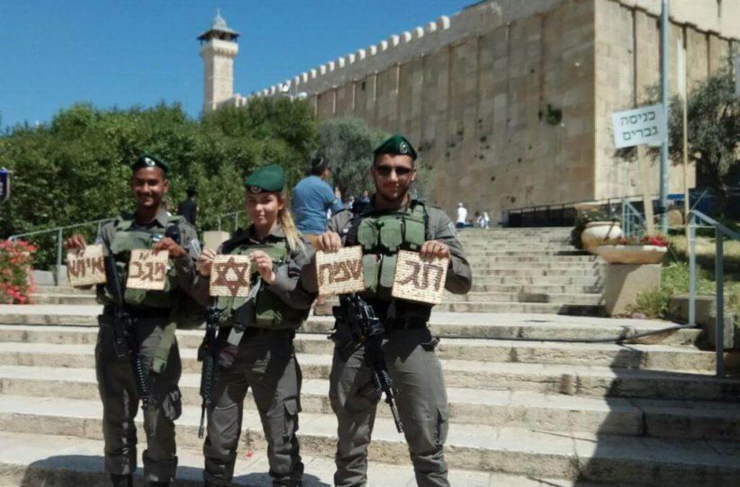Soldiers holding matza outside the Cave of the Patriarchs
